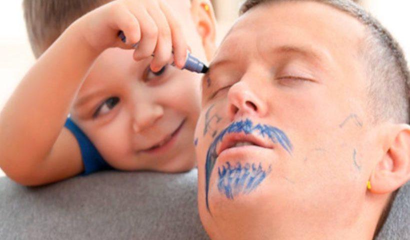 Niño pintando a su padre dormido